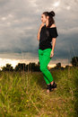 Fashion portrait of a woman with interesting hairdo posing outdoors young brunette outside wearing bright green pants Royalty Free Stock Images