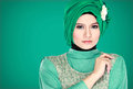 Fashion portrait of young beautiful muslim woman with green cost costume wearing hijab isolated on background Stock Photography