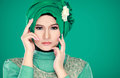 Fashion portrait of young beautiful muslim woman with green cost costume wearing hijab isolated on background Stock Images