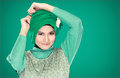 Fashion portrait of young beautiful muslim woman with green cost costume wearing hijab isolated on background Royalty Free Stock Photography