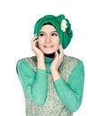 Fashion portrait of young happy beautiful muslim woman with gree green costume wearing hijab and looking up isolated on white Stock Image