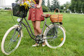 Fashion portrait of young pretty woman with bicycle and flowers Stock Photos