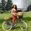 Fashion portrait of young pretty woman with bicycle and flowers Royalty Free Stock Image