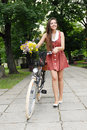 Fashion portrait of young pretty woman with bicycle and flowers Stock Image