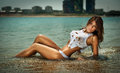Fashion portrait of young sexy brunette girl in bikini and wet t shirt at the beach sensual attractive woman water wearing Stock Image