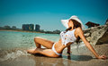 Fashion portrait of young sexy brunette girl in bikini and wet t shirt at the beach sensual attractive woman water wearing Royalty Free Stock Images