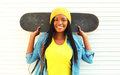 Fashion portrait young smiling african woman with skateboard in colorful clothes over white Royalty Free Stock Photo