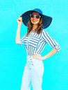Fashion portrait young smiling woman wearing a straw hat, white pants over colorful blue background posing in city Royalty Free Stock Photo