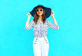 Fashion portrait young smiling woman wearing straw hat, white pants over colorful blue background posing in city Royalty Free Stock Photo