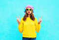 Fashion pretty cool girl in headphones listening to music wearing colorful pink hat yellow sunglasses and sweater over blue Royalty Free Stock Photo
