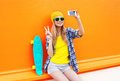 Fashion pretty cool girl makes self portrait on smartphone over colorful orange Royalty Free Stock Photo