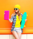 Fashion pretty cool girl makes self portrait on tablet pc over colorful orange Royalty Free Stock Photo