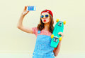 Fashion pretty cool girl is taking picture self portrait on a smartphone over white Royalty Free Stock Photo