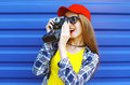 Fashion pretty cool girl wearing a colorful clothes with old retro camera shooting Royalty Free Stock Photo