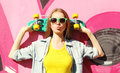 Fashion pretty cool girl wearing a sunglasses and skateboard having fun in city Stock Photography