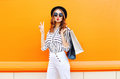 Fashion pretty cool young girl with shopping bags wearing a black hat white pants over colorful orange Royalty Free Stock Photo
