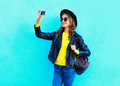Fashion pretty cool young girl taking photo makes self portrait on smartphone wearing a black rock style clothes over blue Royalty Free Stock Photo