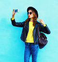 Fashion pretty cool young girl taking photo makes self portrait on smartphone wearing black rock style clothes over colorful blue Royalty Free Stock Photo