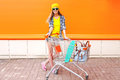 Fashion pretty girl with shopping trolley cart and skateboard over colorful orange