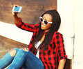 Fashion pretty smiling african woman is taking picture self portrait on smartphone having fun in city Royalty Free Stock Photo