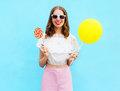 Fashion pretty smiling woman with air balloon and lollipop over colorful blue Royalty Free Stock Photo