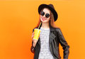 Fashion pretty smiling woman in black rock style with cup over orange background Stock Images