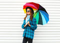 Fashion pretty smiling woman holds colorful umbrella wearing black hat checkered coat jacket over white