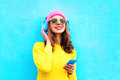 Fashion pretty sweet carefree girl listening to music in headphones with smartphone wearing colorful pink hat yellow sunglasses