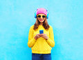 Fashion pretty sweet carefree woman listening music in headphones browsing smartphone wearing colorful pink hat yellow sunglasses Royalty Free Stock Photo