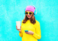 Fashion pretty sweet carefree woman listening music in headphones browsing using smartphone wearing a colorful pink hat Royalty Free Stock Photo