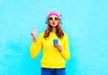Fashion pretty sweet carefree woman listening music in headphones with smartphone wearing a colorful pink hat yellow sweater Royalty Free Stock Photo