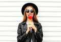 Fashion pretty sweet young woman enjoying a taste lollipop heart wearing black hat leather jacket over white Royalty Free Stock Photo