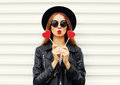 Fashion pretty sweet young woman with red lips making air kiss with lollipop heart wearing black hat leather jacket over white Royalty Free Stock Photo