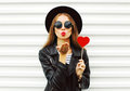 Fashion pretty sweet young woman with red lips sends air kiss with lollipop heart wearing black hat leather jacket over white Royalty Free Stock Photo