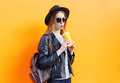 Fashion pretty woman in black rock style drinking from cup over orange background a Stock Photography