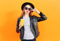 Fashion pretty woman in black rock style having fun over orange background Stock Photo