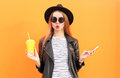 Fashion pretty woman with cup and smartphone in rock black style over colorful orange background Royalty Free Stock Photography