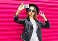 Fashion pretty woman makes self portrait on smartphone in black rock style over city pink Royalty Free Stock Photo