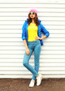 Fashion pretty woman model in colorful clothes over white background wearing pink hat yellow sunglasses and blue jacket Royalty Free Stock Photo