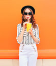 Fashion pretty woman model with fresh fruit juice cup wearing black hat white pants over colorful orange Royalty Free Stock Photo