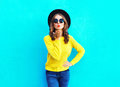 Fashion pretty woman sends air sweet kiss wearing a black hat and yellow knitted sweater over colorful blue Royalty Free Stock Photo