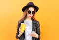 Fashion pretty woman using smartphone in rock black style over orange background Royalty Free Stock Photography