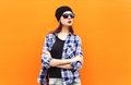 Fashion pretty woman wearing a black hat, sunglasses and checkered shirt over colorful