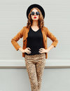 Fashion pretty woman wearing black hat, sunglasses and jacket over urban background Royalty Free Stock Photo
