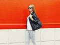 Fashion pretty woman wearing a rock black leather jacket sunglasses and bag in profile over red background Royalty Free Stock Photos