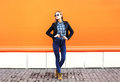 Fashion pretty woman wearing rock black style over orange background Royalty Free Stock Photography