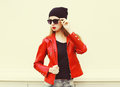 Fashion pretty woman wearing a rock red leather jacket, sunglasses and black hat Royalty Free Stock Photo