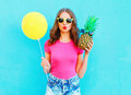 Fashion pretty woman with yellow air balloon and pineapple wearing a pink t-shirt over colorful blue Royalty Free Stock Photo