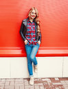 Fashion pretty young blonde smiling woman wearing a black rock style posing over colorful red Royalty Free Stock Photo
