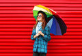 Fashion pretty young smiling woman holds colorful umbrella wearing black hat checkered coat jacket over red